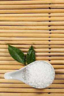 Deux feuilles vertes et le sel de mer dans une cuillère