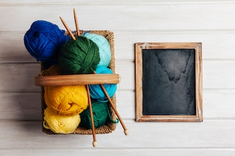 Différentes boules de laine dans le panier à côté de l'ardoise