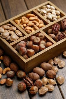 Différents écrous dans une boîte en bois