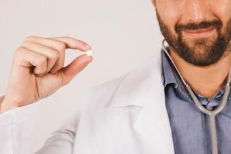 Docteur souriant et tenant une pilule