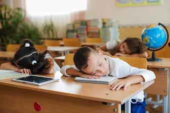 Écoliers appuyés sur la table en sommeil