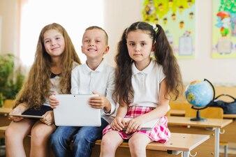 Écoliers posant en classe