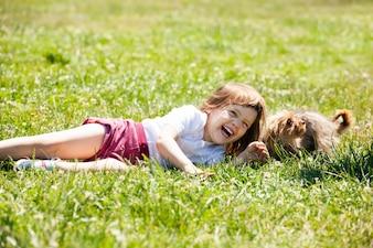 Enfant heureux jouant avec un chiot à la prairie en été