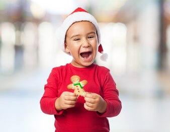 Enfant Joyful posant avec un délicieux biscuit