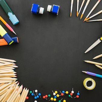 Ensemble de matériel scolaire sur bureau noir