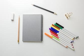 Espace de travail minimal - Photo créative d'une table plate de bureau d'espace de travail avec carnet de croquis et crayon en bois sur fond blanc de copie. Vue de dessus, photographie à plat.