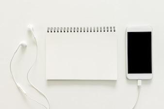 Espace de travail minimal - Photo de bureau de travail créative avec un carnet de croquis et un téléphone portable avec écran vierge sur fond blanc de copie. Vue de dessus, photographie plate.