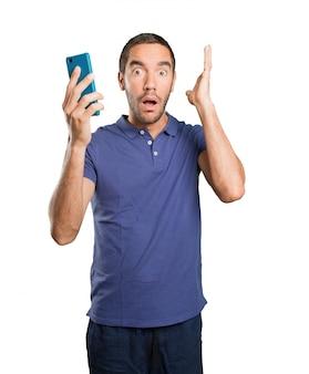 Étonné jeune homme utilisant un téléphone portable sur fond blanc