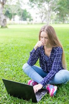 Étudiant occupé utilisant un ordinateur portable tout en préparant la recherche