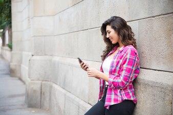 Étudiant positif appuyé sur le mur et utilisant un téléphone