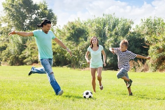 Famille avec adolescent jouant au football