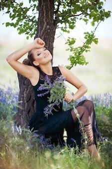 Femme appuyée sur un arbre