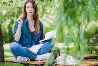 Femme avec des cahiers dans le parc