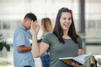 Femme avec livre gesticulant ok