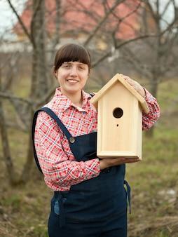 Femme avec nouvelle maison d'oiseaux