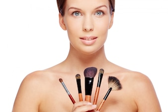 Femme avec pinceaux de maquillage