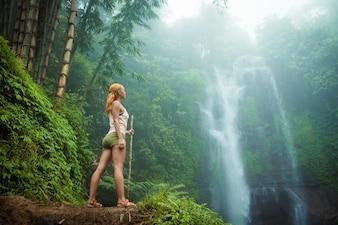 Femme aventurière regarde la cascade