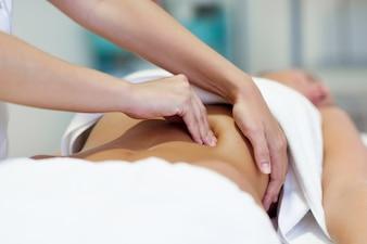 Femme ayant un massage de l'abdomen par un thérapeute professionnel en ostéopathie