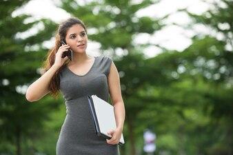 Femme confiante avec des documents parlant au téléphone