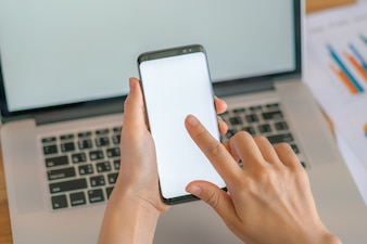 Femme d'affaires avec des graphiques financiers et un téléphone mobile sur un ordinateur portable sur la table.