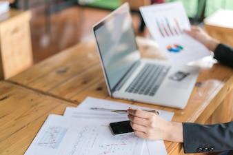 Femme d'affaires avec des tableaux financiers et un ordinateur portable sur la table.