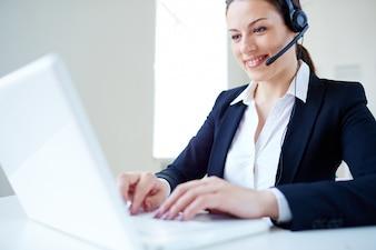 Femme d'affaires en utilisant un casque et un ordinateur portable
