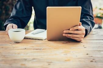 Femme d'affaires main tenant la tablette sur la table au café avec filtre vintage tonifié.