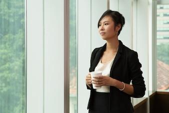Femme d'affaires pensive debout avec une tasse à café