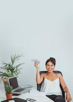 Femme d'affaires s'amuser avec un avion en papier