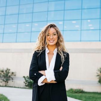 Femme d'affaires souriant devant le bâtiment en verre
