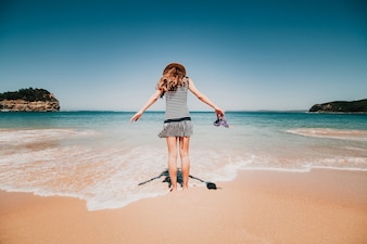 Femme dans son dos entrant dans une belle plage australienne.