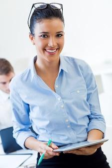 Femme debout dans le bureau et l'utilisation de la tablette