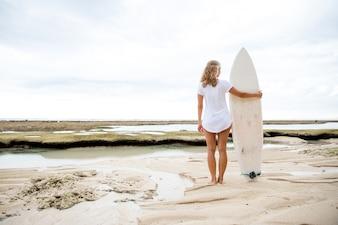 Femme, debout, sable, plage, planche de surf