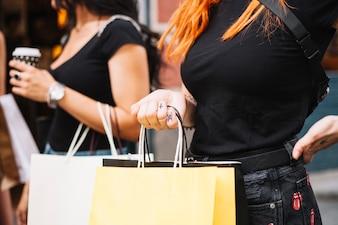 Femme en noir tenant des sacs en papier