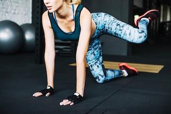 Femme en vêtements de sport soulevant la jambe gauche