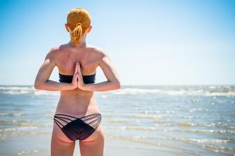 Femme faisant le yoga namaste inversé