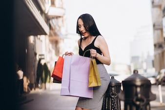 Femme habillée à la mode avec des sacs à provisions colorés dans les rues, concept d'achat