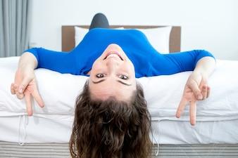Femme ludique montrant des signes de victoire sur le lit