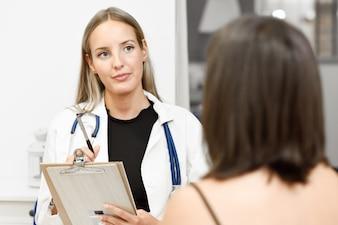 Femme médecin expliquant le diagnostic à sa jeune femme patiente.