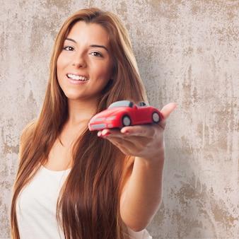 Femme montre voiture jouet.