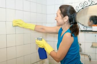 Femme mûre nettoie la tuile dans la salle de bain