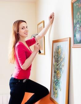 Femme positive accrochant les photos d'art