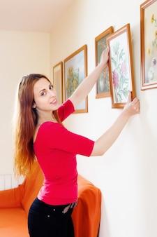 Femme positive en rouge accrochant les photos d'art