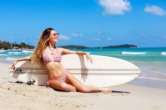 femme Ravie assis sur le sable avec sa planche de surf