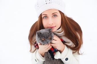 Femme rousse étreindre son chat sur fond blanc