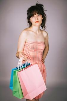 Femme sceptique avec des sacs en papier