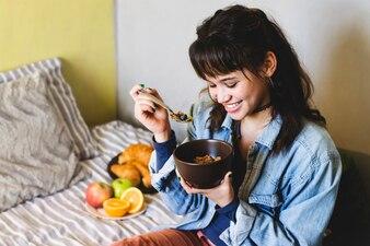 Femme souriante avec bol de céréales