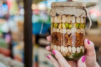 Femme souriante tenant un pot de mélange de fruits secs et de miel fait maison.