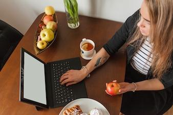 Femme tatouée à la vue supérieure de l'ordinateur portable
