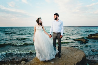 Femme tenant son mari par la mer